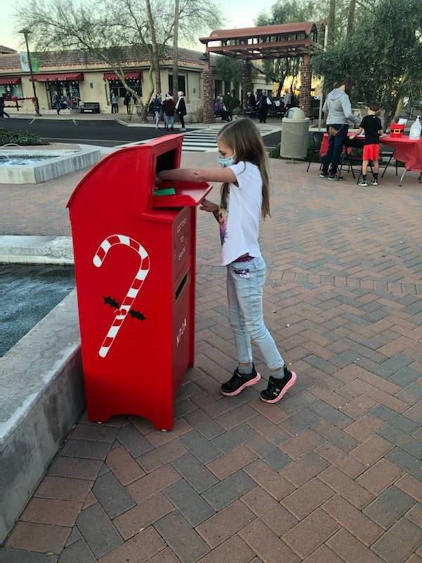 child dropping a letter to Santa into the box